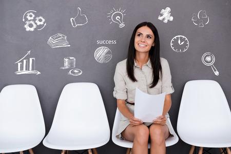 Berzeugte junge Geschäftsfrau, die Papier, während sitzt auf dem Stuhl vor grauem Hintergrund Standard-Bild - 43296942