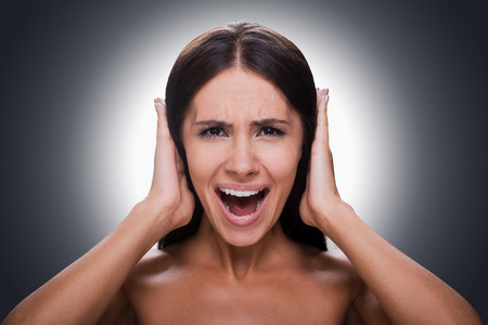 hands covering ears: Portrait of frustrated young shirtless woman shouting and covering ears by hands while standing against grey background