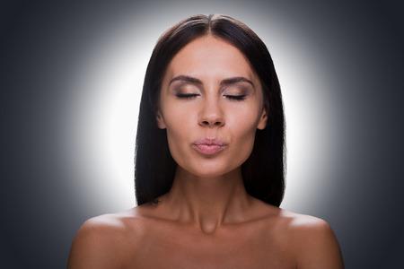 beso labios: Retrato de hermosas j�venes sin camisa mujer manteniendo los ojos cerrados y haciendo muecas mientras est� de pie contra el fondo gris