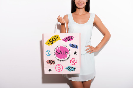 fashion shopping: Cropped image of cheerful young woman in dress standing against white background and carrying shopping bag with colorful sketches on it