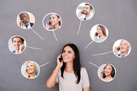 personas hablando: Mantenerse en contacto. Joven y bella mujer hablando por teléfono móvil y sonriendo con los retratos de diversas personas sobre su cabeza