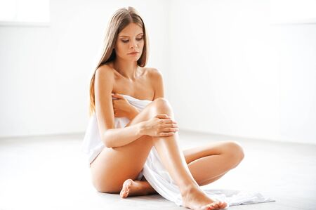 naked woman sitting: Pure and sensual. Attractive young naked woman covering herself with white textile while sitting on the floor