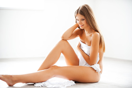 young woman nude: Natural and beautiful. Smiling young woman covering herself with white textile while sitting on the floor