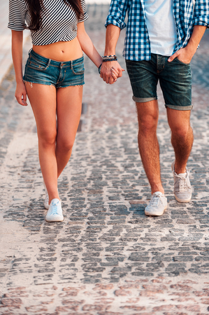 holding hands while walking: Walking together. Close-up of young loving couple holding hands while walking along the street Stock Photo