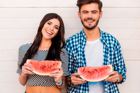 food woman: Sweet and juicy like their love. Cheerful young loving couple holding slices of watermelon and looking at camera while standing outdoors togehter