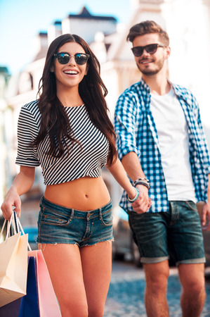 couple dating: Shopping together. Cheerful young loving couple holding hands and smiling while walking along the street
