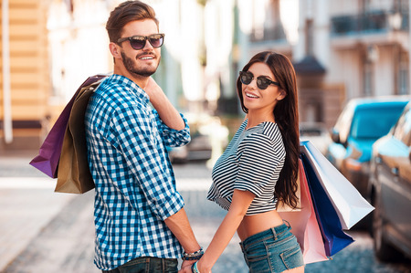 retail scene: Quality time together. Beautiful young loving couple carrying shopping bags on shoulders and holding hands while walking along the street Stock Photo