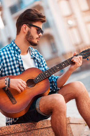 freedom concept: He loves that sound. Low angle view of handsome young man playing guitar whilesitting outdoors