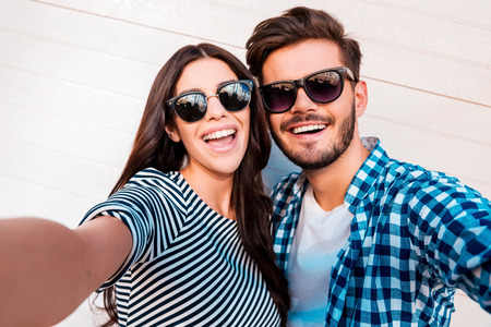 making love: Capturing bright moments. Joyful young loving couple making selfie on camera while standing outdoors Stock Photo