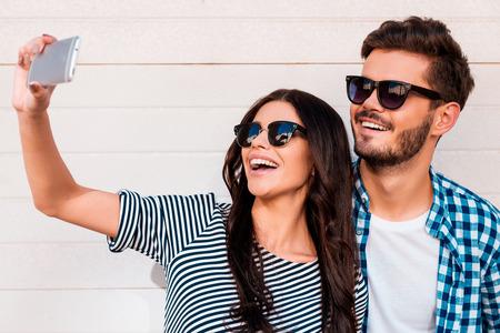 haciendo el amor: Hora de hacerse un selfie. Joven y bella selfie toma pareja de enamorados en el teléfono inteligente mientras está de pie al aire libre