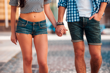 holding hands while walking: Just you and me. Close-up of beautiful young loving couple holding hands while walking along the street Stock Photo