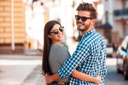 casal: Tão felizes juntos. Sorrindo jovem casal se abraçando amorosa e olhar câmera t durante a caminhada ao longo da rua Imagens