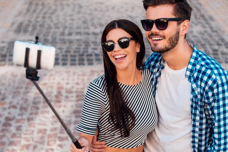 haciendo el amor: Diversión selfie. Vista superior de la hermosa joven que hace pareja amorosa selfie en el teléfono inteligente mientras está de pie al aire libre