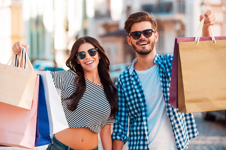 They love shopping together. Cheerful young loving couple stretching out shopping bags and smiling while walking along the street Archivio Fotografico