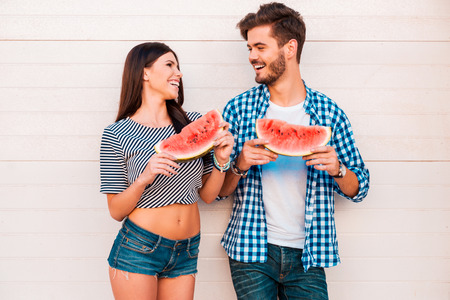 couple dating: Watermelon lovers. Happy young loving couple holding slices of watermelon and looking at each other while standing outdoors