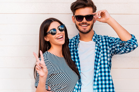 couple dating: Peace out! Happy young loving couple looking at camera and smiling while standing outdoors