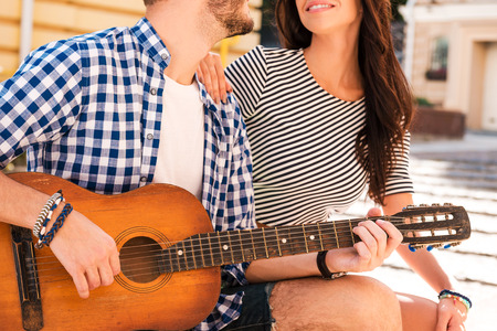 serenade: City serenade. Cropped image of beautiful young loving couple bonding to each other while sitting together outdoors Stock Photo
