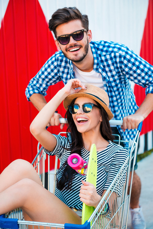 shopping scene: Summer fun. Top view cheerful young woman sitting in shopping cart while her boyfriend pushing it Stock Photo