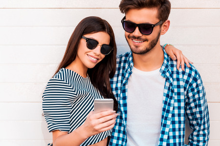 couple dating: Look at this photo! Beautiful young woman showing something on her mobile phone to her boyfriend while standing outdoors together Stock Photo