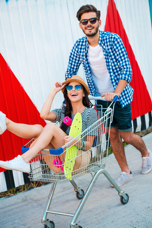 shopping cart: They always have fun together. Top view of joyful young woman sitting in shopping cart while her boyfriend pushing it Stock Photo