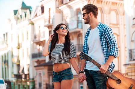 City romance. Smiling young loving couple holding hands and looking at each other while walking along the street Stock Photo
