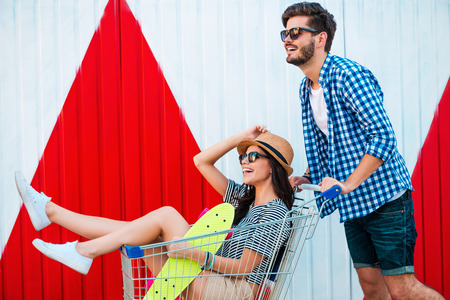 shopping cart: Carefree fun. Side view of cheerful young woman sitting in shopping cart while her boyfriend pushing it
