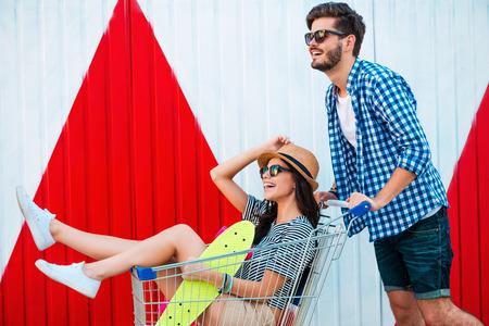 mujer alegre: Diversión despreocupada. Vista lateral de la mujer joven alegre sentado en la cesta mientras que su novio empujándolo