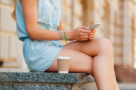 mujer alegre: conexión urbana. Primer plano de una mujer joven que sostiene el teléfono móvil mientras se está sentado al aire libre