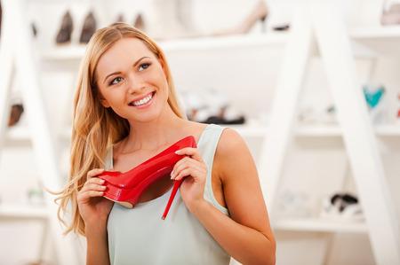 tienda de zapatos: Me encanta que los zapatos! Sonriente mujer joven con el zapato rojo y mirando de lejos mientras est� de pie en la tienda de zapatos