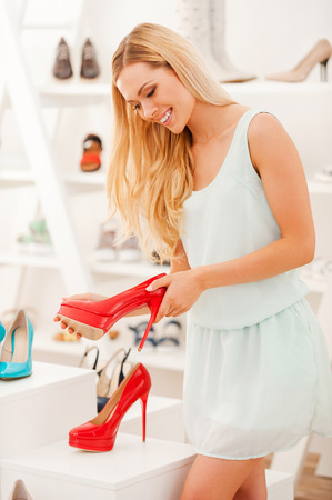 shoe store: These are perfect! Smiling young woman holding red shoe and looking at it while standing in the shoe store Stock Photo