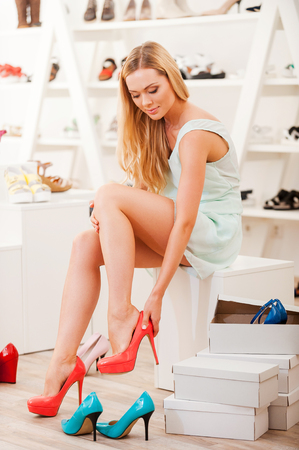 shoes woman: I hope they will fit. Beautiful young woman trying on different shoes while sitting in shoe store
