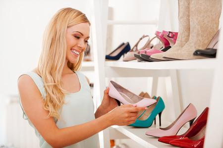 comprando zapatos: Tratar a sí misma por las compras. Feliz mujer joven que elige los zapatos y sonriendo mientras está de pie en la tienda de zapatos