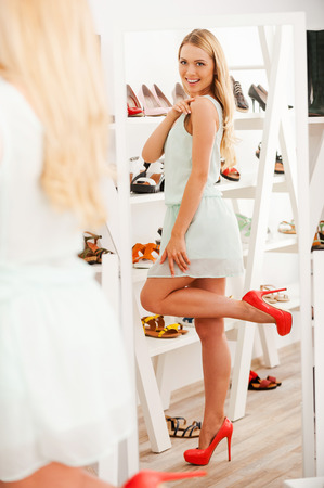 full length mirror: Fit for princess! Full Length of smiling young woman trying on new shoes and looking in the mirror while standing in shoe store