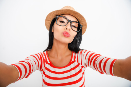 sex symbol: Kiss me! Beautiful young woman making selfie on camera while standing against white background