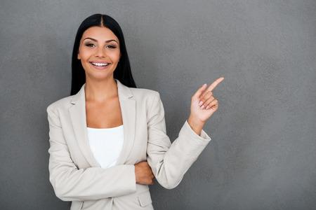 secretaries: Hermoso y fiable. Empresaria joven sonriente que mira la cámara y apuntando hacia afuera de pie sobre fondo gris Foto de archivo