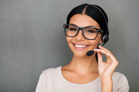 woman on phone: Service with happy smile. Cheerful young female customer service looking at camera and smiling while standing against grey background
