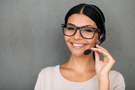 servicio al cliente: Servicio con sonrisa feliz. Servicio femenina joven alegre al cliente mirando a la cámara y sonriendo mientras está de pie contra el fondo gris