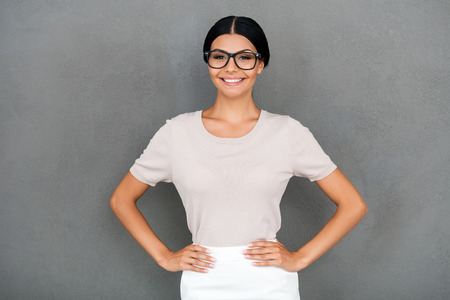 hand on hip: Proud of being herself. Smiling young businesswoman holding hands on hips and looking at camera while standing against grey background
