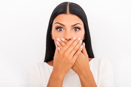 attractive people: Shocking news. Surprised young woman covering mouth with hands and staring at camera while standing against white background Stock Photo
