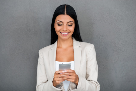 this: This mobile phone is for smart people. Smiling young businesswoman holding mobile phone while standing against grey background