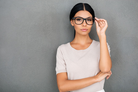 adjusting: Confident beauty. Confident young businesswoman adjusting eyewear and looking at camera while standing against grey background