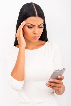 mobile phone: Bad news. Frustrated young woman holding mobile phone and touching her head while standing against white background