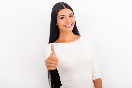 women smiling: I approve! Smiling young woman showing her thumb up while standing against white background