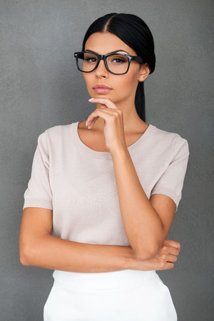 mujer pensativa: Confident in her forces. Thoughtful young businesswoman holding hand on chin and looking at camera while standing against grey background Foto de archivo