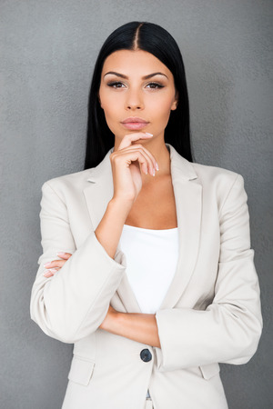 Thinking about solution. Thoughtful young businesswoman holding hand on chin and looking at camera while standing against grey background Stock Photo