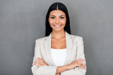 standing against: Charming businesswoman. Smiling young businesswoman keeping arms crossed and looking at camera while standing against grey background
