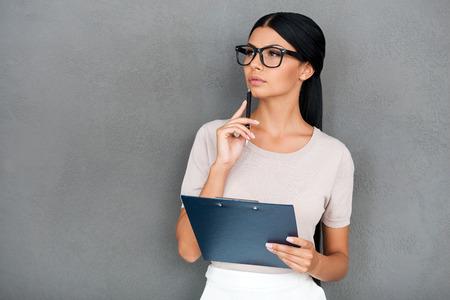 mujer pensativa: Haciendo la planificaci�n de negocios. Reflexiva joven empresaria celebraci�n de portapapeles y mirando a otro lado mientras est� de pie contra el fondo gris