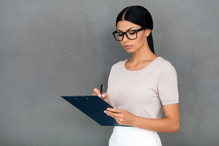 portapapeles: Confident businesswoman. Confident young businesswoman writing in clipboard while standing against grey background