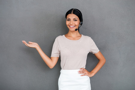 call center representative: Happy to help you. Smiling young female customer service holding copy space on her hand and looking at camera while standing against grey background