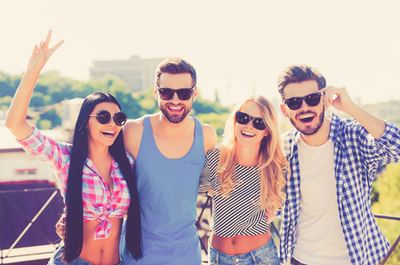 four people: Having fun with friends. Group of cheerful young people bonding to each other and looking at camera while standing on the roof